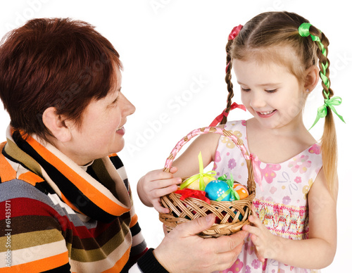 Little girl and her grandmother with basket full of easter eggs