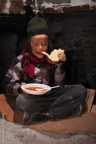 Young homeless boy eating on the street