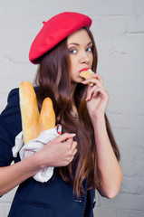 Beautiful young Frenchwoman eating baguette
