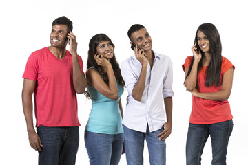 Group of young Indian friends using their smartphones.