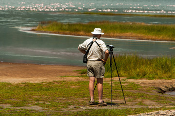 Tourist observing birds and taking photos by the lake