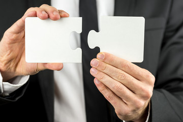 Businessman holding two pieces of a blank puzzle
