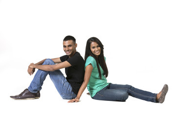 Cheerful young Indian couple sitting with back to each other on