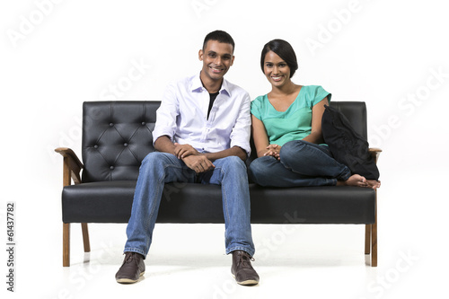 Cheerful young Indian couple sitting on a retro sofa.