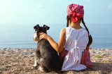 beautiful girls embracing her dog looking at the sea