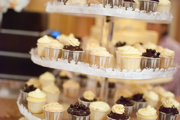 Assorted wedding cup cakes on a multi-level tray