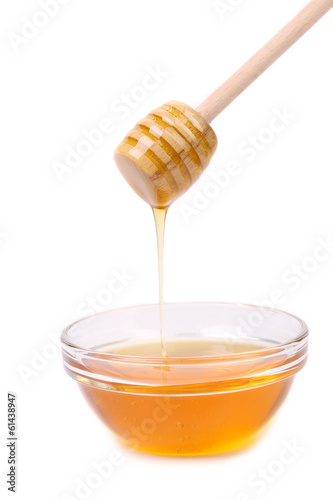 Honey dripping from a wooden dipper.