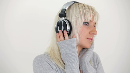 Beautiful blonde woman listening to music in headphones