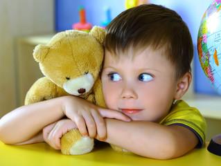 Smiling boy with a soft toy teddy bear