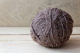 Brown ball of yarn on a wooden table over vintage wallpaper
