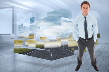 Composite image of serious businessman standing with hands in po