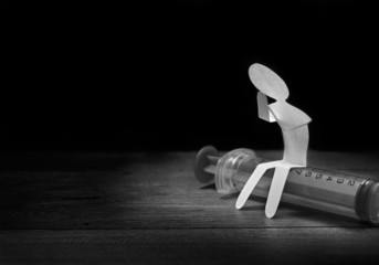 Lonely paper man sitting on syringe