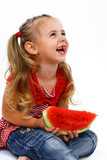 Little smiling girl eating watermelon