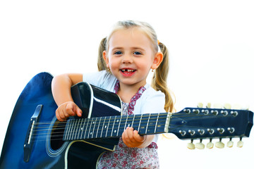 Little smiling girl playing guitar