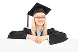 Female student in graduation gown posing behind blank panel