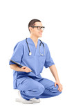 Male medical worker crouching and holding clipboard