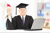 Mature man in graduation gown posing with diploma and laptop