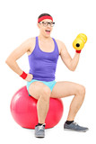 Nerdy guy sitting on pilates ball and lifting a dumbbell