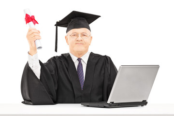 Mature man in graduation gown posing with diploma and laptop on