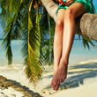 Woman sitting on a palm tree at tropical beach