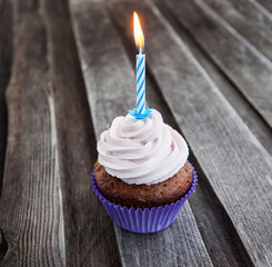 Tasty birthday cupcake with candle