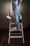 Man working on ladder with drill