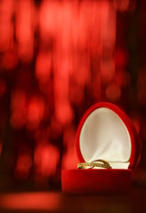 złoty pierścionek w czerwonym pudełku na czerwonym tle pion