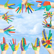 Painted hands with smile on sky background