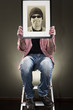 Man holding picture frame while sitting on a ladder