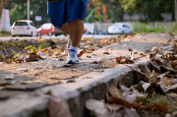 close up of feet of a runner running in autumn