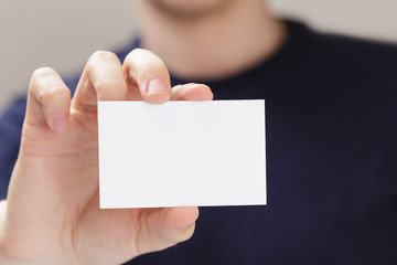 adult man hand  holding empty business card in front of camera
