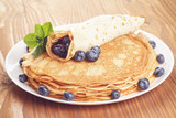 russian pancakes with blueberries on wooden table