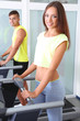 Guy and girl on treadmills at gym