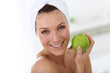 Woman with towel in hair holding green apple