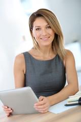 Businesswoman in office working on digital tablet
