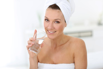 Attractive woman in bathroom drinking water