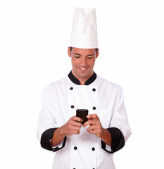 Professional young chef texting a message