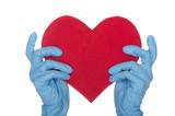 Two hands in blue medical gloves keep heart