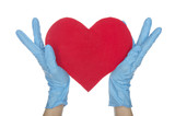 Hands in blue medical gloves keep heart