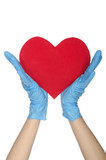 Two hands in medical gloves keep heart