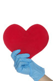 One arm in blue medical gloves keep heart