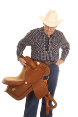 Elderly man cowboy saddle look down
