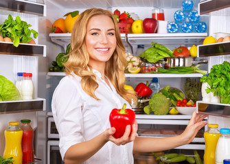 Housewife at the kitchen take red pepper from fridge