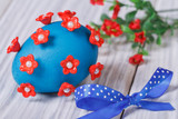 Blue easter egg decorated with red flowers with bow