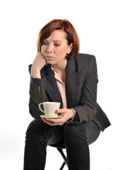 sad business woman with red hair drinking coffee and thinking