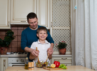 father and his son preparing a salad in the kitchen.