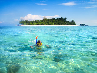 Little boy snorkeling next to a beautiful tropical island