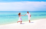 Young beautiful couple dancing on the beach of a tropical paradi
