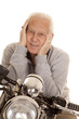 Elderly man on motorcycle close hands face