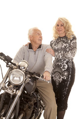 Elderly couple him on motorcycle her stand